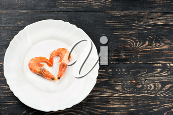 Boiled shrimp in a heart shape on the plate on a wooden background