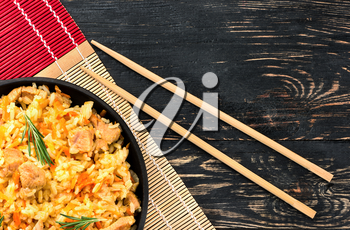 Asian pilaf in portioned frying pan on a bamboo napkin with chopstick