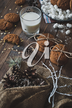 Milk and cookies on wooden table.