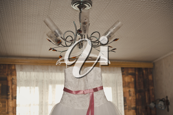 The white beautiful wedding dress hangs on a chandelier.