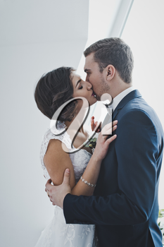 Young husband and wife gently kiss each other on the bright background of the window.