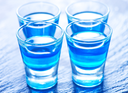 blue alcoholic drink into small glasses on a table