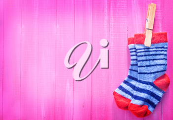 baby socks on the pink wooden table