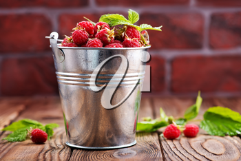 raspberry in metal bowl and on a table