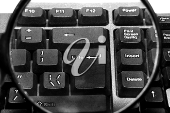 Computer keyboard with magnifying glass close up
