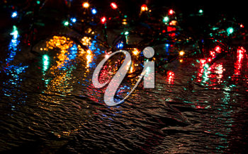 Multi-colored lights on a dark background on a reflective surface