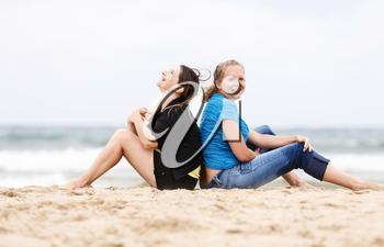 Two pretty young smiling women sitting and relaxing on the sand on the seashore. Two girls resting on the beach. Two cheerful young woman outdoors. Selective focus on the models.