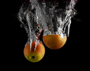 Apples are falling into the water with a splash on a black background.