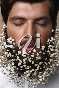 Creative Portrait of young beautiful man with a beard decorated with flowers.