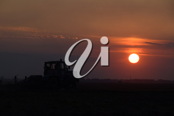 Tractor plowing plow the field on a background sunset. tractor silhouette on sunset background.