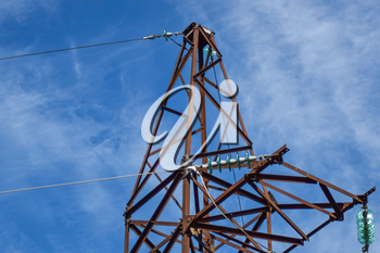 Supports high-voltage power lines against the blue sky with clouds. Electrical industry.