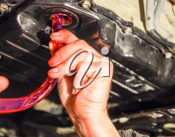 Oil change in automatic transmission. Filling the oil through the hose. Car maintenance station. Red gear oil. The hands of the car mechanic in oil.