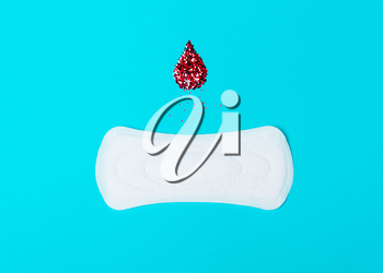 menstrual pads with a drop of blood on a blue background. Concept of critical days,  cycle, menstruation