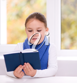 Cute little girl is reading book while sitting at table, indoor shoot
