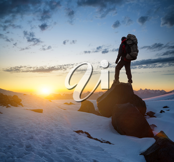 Silhouette of a tourist on the peak of high rocks. Sport and active life concept