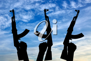 Terrorists concept. Weapons in the hands of terrorists, against the sky