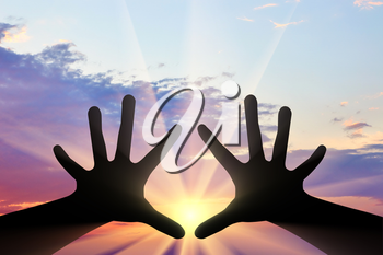 Religion and God. Silhouette of hands raised to the sky at sunset