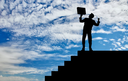 Business success concept. Silhouette of a happy businessman with a briefcase in his hands at the height of the steps on the sky background