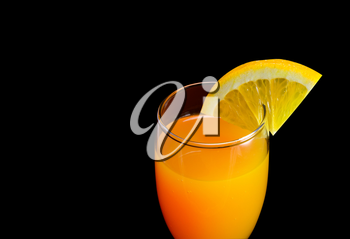 Mimosa cocktail with a slice of orange on a black background closeup