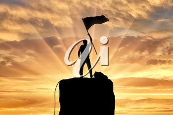 Silhouette of a climber on a mountain top with a flag in his hand. Concept of success and motivation