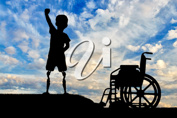 Children with disabilities concept. Happy disabled boy with a prosthetic legs standing near a wheelchair against the sky