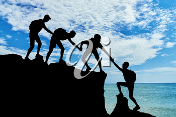 Men climbers help each other in the mountains against the background of the sea. Conceptual scene of male mountaineers work in a team