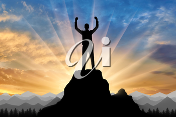 Silhouette of a happy mountaineer on top of a mountain. Conceptual scene of happiness