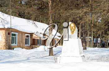 Old rural hospital. Nearby there is a monument to Vladimir Ilyich Lenin. Russia.