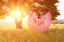 Young woman standing on a wheat field with sunrise on the background. Beauty Romantic Girl Outdoors. The dress fluttering in the wind at sunset. flying fabric.