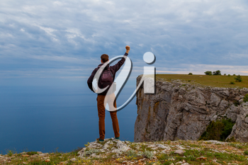 Man on top of mountain. Conceptual design.Young man with backpack standing with raised hands on top of a mountain and enjoying valley view. The idea of victory and the championship