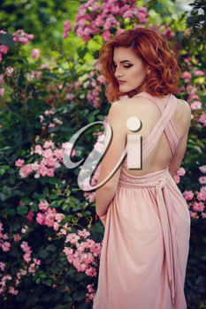 Lovely young woman in a pink dress and red hair, waiting for a date. A walk through the summer city, pink flowering bushes