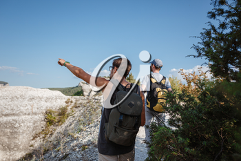 Two Hikers with Backpacks and other climbing Gear staying on top of Rock. man pointing with his hand discussing route. Plan, vision and mission concept.