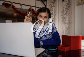 Happy asian woman wearing blue sweater holding glass of champagne, talking with family, social distance friend by video conference call meeting chat at home. stay home vocation, Christmas party online