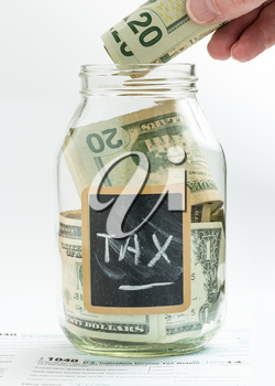 Caucasian hand putting money into glass jar on white background with black chalk label or panel and used for saving US dollar bills for a tax bill