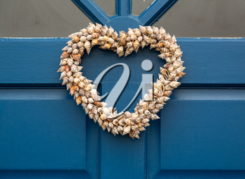 Heart shaped front door wreath made out of cone shapes of sea shells