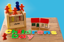 Childs wooden blocks and magnetic letters spell out Children's Day for June first