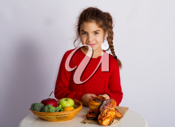 Little girl chooses what to eat, healthy food or buns