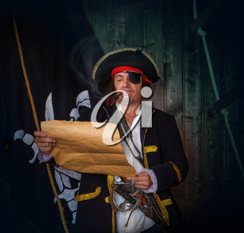 Adult pirate captain in a traditional costume and with arms looks at a treasure map against the backdrop of a jolly roger