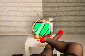 The girl sits in front of a small old TV on which the green screen is throwing her legs in bright red shoes on the table.