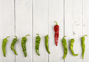 Leadership concept - red hot chili pepper leading the group of green peppers