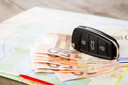 Car rental concept - car key and money on the road map