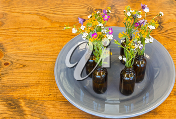 Gray Plate With Small Vases With Flowers Sitting on Wooden Table