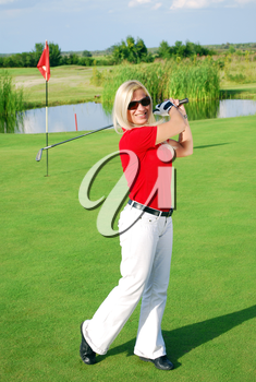 Happy blonde girl playing golf