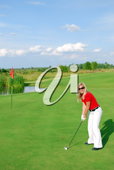 Blonde girl golf player on golf field