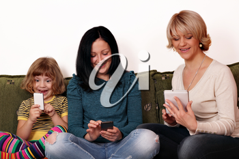 happy mother and daughters playing with smart phones and tablet
