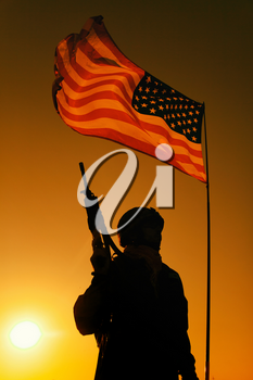 Silhouette of US army infantry soldier, special forces rifleman veteran, armed assault rifle standing under waving United States of America national flag with setting sun on background
