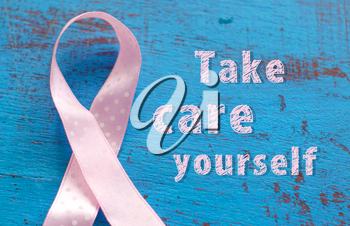 Breast cancer awareness ribbon on the blue wooden background.