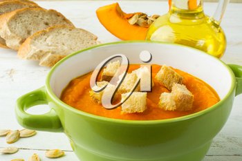 Creamy pumpkin squash vegetable soup with croutons in a green bowl and bread on white wooden background