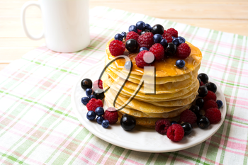 Breakfast pancakes with honey and fresh berries and coffee mug.  Homemade pancakes served with blueberry, raspberry and blackcurrant.