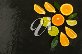 Detox concept with lemon, orange and lime on black background. Healthy eating concept with ripe mixed citrus. Lime, lemon and orange fruit background.